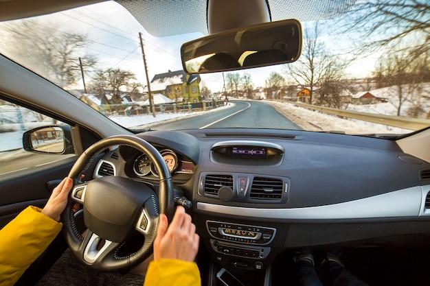 Interior de carro moderno com mãos femininas motorista no volante, paisagem de inverno nevado lá fora. conceito de condução segura.