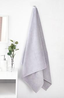 Interior de casa de banho branco com toalha de terry cinza, itens de banheiro e buquê de flores de suspensão