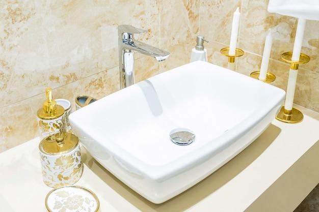 Interior de casa de banho com lavatório e torneira.