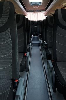 Interior de corredor de ônibus vazio e limpo com fileiras de assentos de tecido preto