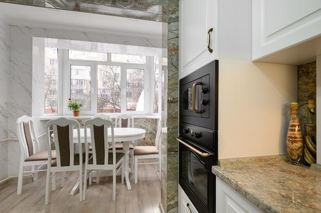 Interior de cozinha branca clássica moderna com zona de refeições