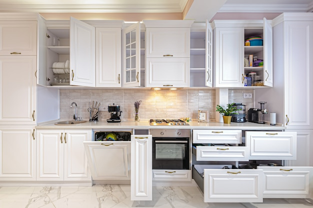 Interior de cozinha branca moderna de luxo com portas abertas e gavetas