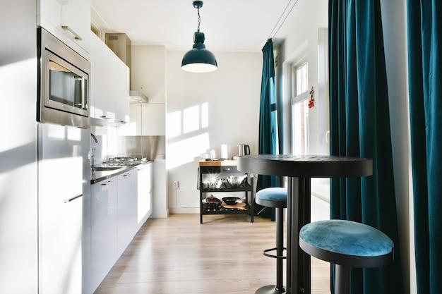 Interior de cozinha contemporânea com diversos aparelhos e mesa com banquetas em apartamento