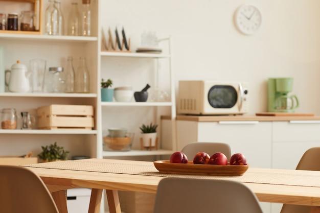 Interior de cozinha em tons quentes com design minimalista e mesa de madeira em primeiro plano