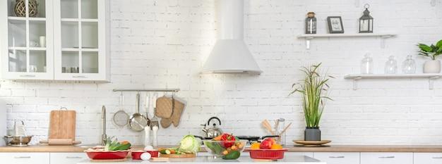 Interior de cozinha moderna e elegante com legumes e frutas na mesa.
