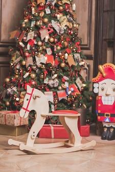 Interior de decoração de sala de natal com cadeira de cavalo, árvore do ano novo e quebra-nozes.
