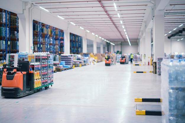 Interior de edifício industrial de armazém com pessoas e empilhadeiras manuseando mercadorias na área de armazenamento