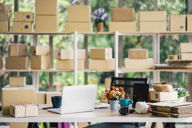 Interior de escritório em casa de inicialização com caixa de encomendas nas prateleiras, laptop, xícara de café e scanner de código de barras em cima da mesa, espaço de trabalho