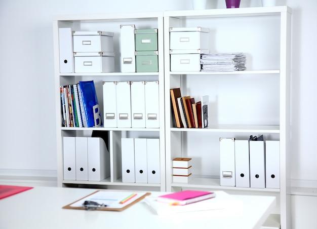 Interior de escritório moderno com mesas, cadeiras e estantes