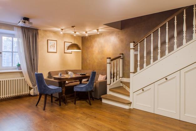 Interior de estilo clássico de um quarto de hóspedes em um apartamento de dois andares. mesa de jantar e cadeiras, escada de madeira branca para o segundo andar com armários embutidos.