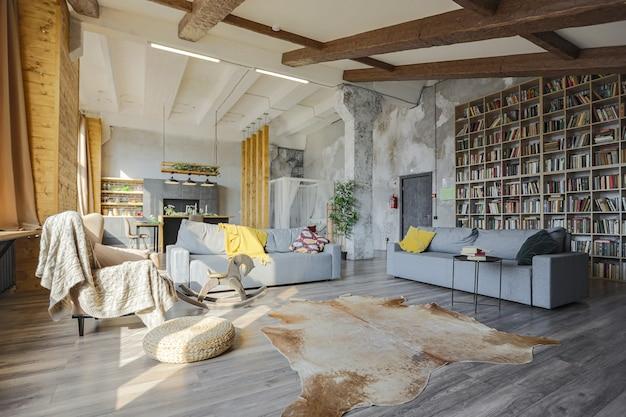 Interior de estilo loft escuro de grande casa de campo aconchegante. apartamento de plano aberto com área de cozinha, área de descanso e área de dormir. janelas enormes e decoração de madeira