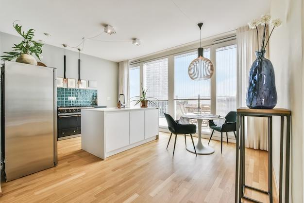 Interior de estilo minimalista de cozinha moderna com área de jantar e janela enorme em apartamento moderno