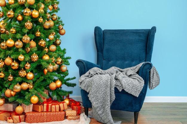 Interior de férias. linda árvore de natal decorada com poltrona azul