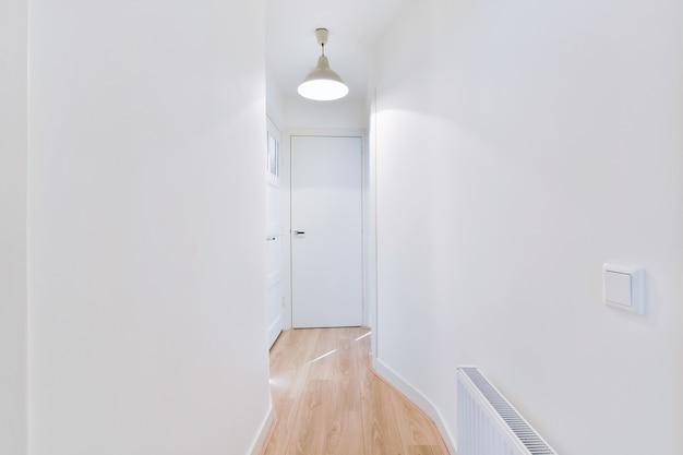 Interior de longo corredor estreito com piso de madeira e paredes brancas em apartamento projetado em estilo minimalista