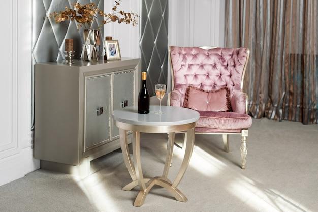 Interior de luxo. luxuosa poltrona de veludo rosa, móveis antigos esculpidos, interior clássico. servido vinho no elegante restaurante à espera de um hóspede.