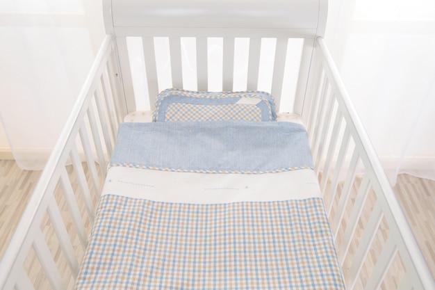 Interior de luz aconchegante sala de bebê com berço e roupa de cama
