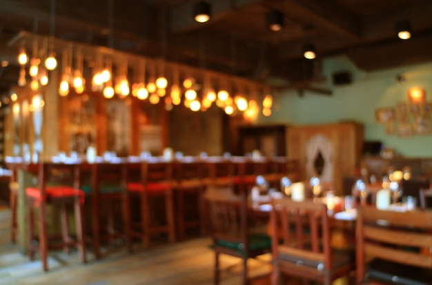 Interior de madeira borrada do restaurante em cores quentes com luz de bokeh