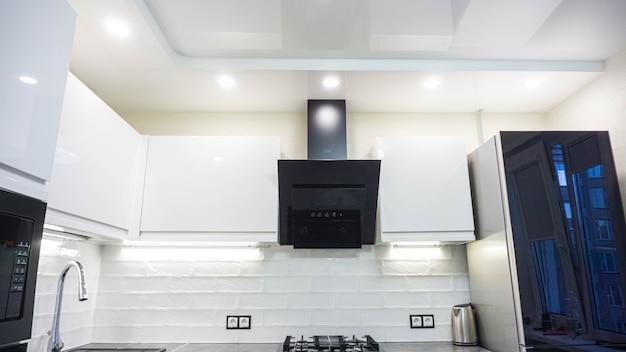 Interior de móveis brancos de uma cozinha compacta, armários brilhantes com eletrodomésticos embutidos