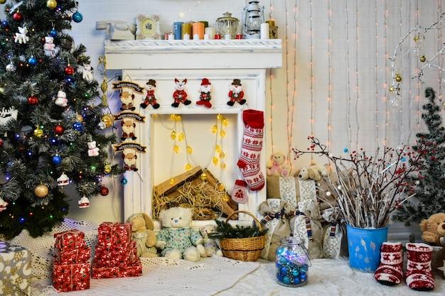 Interior de natal nas cores vermelho e branco com árvore de natal e lareira