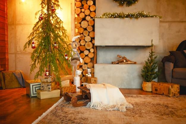Interior de natal no estilo de um loft escandinavo: concreto cinza, decoração em madeira, lâmpadas incandescentes, árvore de natal artificial realista. ano novo aconchegante em casa de campo