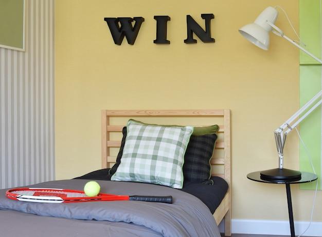 Interior de quarto moderno decorativo com raquete e bola de tênis na cama de madeira