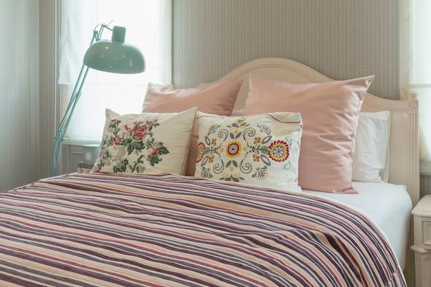 Interior de quarto vintage com almofadas de flores e cobertor listrado rosa na cama