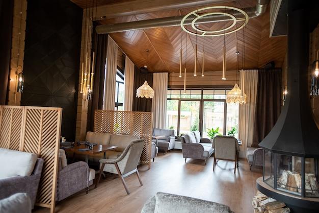 Interior de restaurante elegante e luxuoso com paredes de madeira e lustres sofisticados pendurados sobre as mesas cercados por sofás e poltronas macios