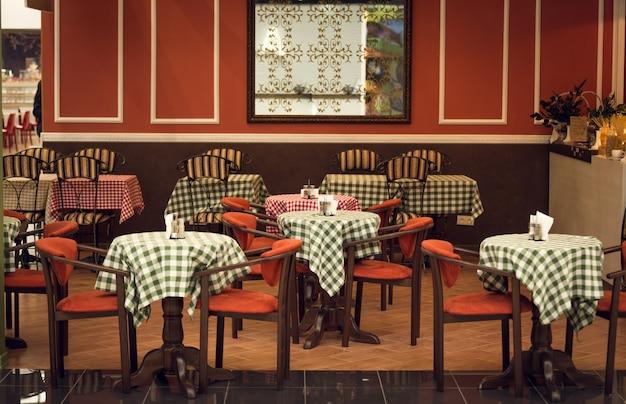 Interior de restaurante italiano com cadeiras e mesas de madeira
