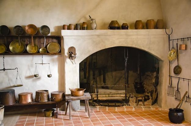 Interior de um antigo castelo com lareira e cozinha.