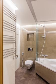 Interior de um banheiro combinado. chuveiro e vaso sanitário embutido no quarto decorado com azulejos de imitação de mármore. há chuveiro sanitário e aquecedor de parede para toalhas.