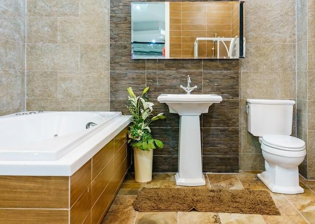 Interior de um banheiro contemporâneo com banheira, em cores naturais da terra.