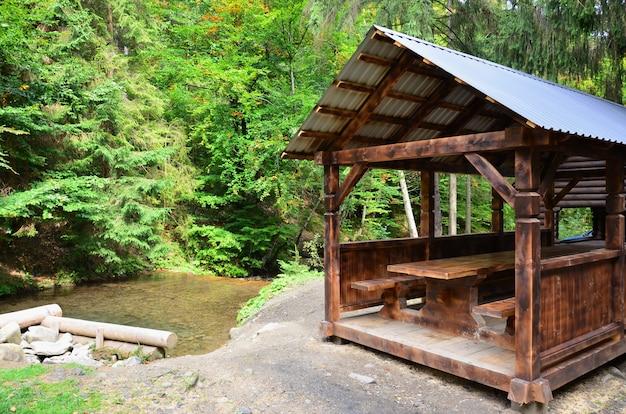Interior de um caramanchão de madeira artesanal de madeira escura na floresta