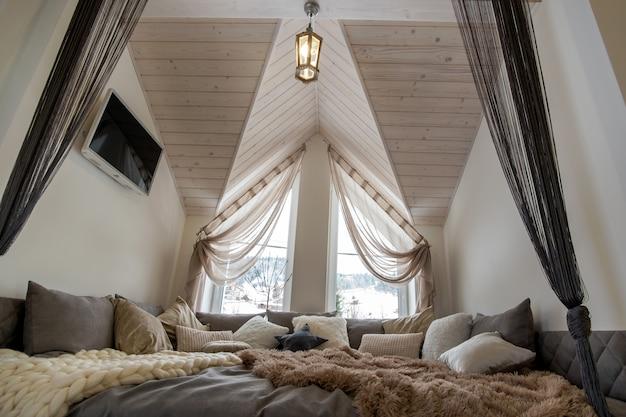 Interior de um corredor espaçoso da casa moderna com grande lugar de descanso macio. sofá largo contemporâneo com muitos travesseiros e teto luminoso de madeira.