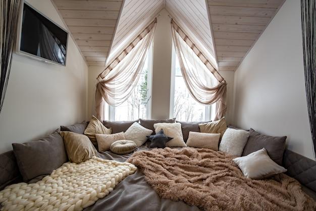 Interior de um corredor espaçoso da casa moderna com lugar de descanso macio grande. sofá largo contemporâneo com muitos travesseiros e teto luminoso de madeira.