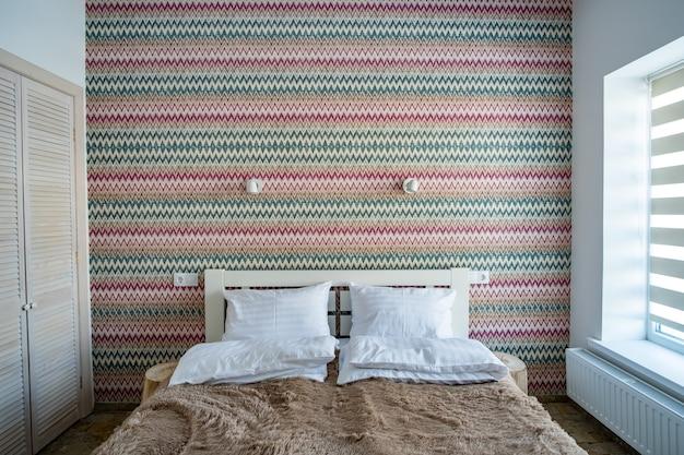 Interior de um espaçoso quarto de hotel com roupa de cama limpa em uma grande cama de casal. quarto contemporâneo aconchegante em uma casa moderna.