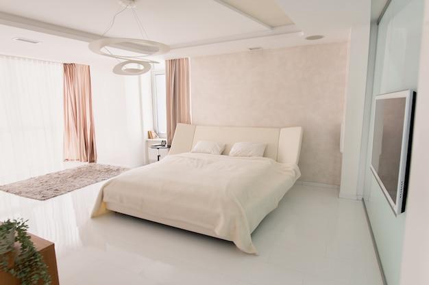 Interior de um grande quarto aconchegante com cama de casal confortável, tv de plasma na parede, despertador na mesa pequena e tapete felpudo cinza no chão