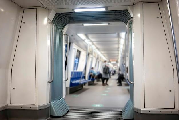 Interior de um metrô com iluminação e poucas pessoas dentro