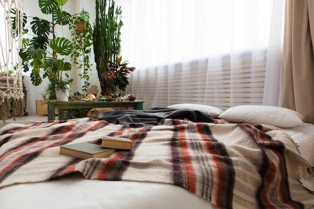 Interior de um moderno estúdio com muitas plantas e uma cama no chão