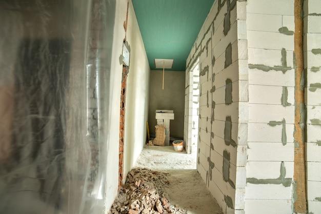 Interior de um quarto de apartamento com paredes nuas e teto em construção.