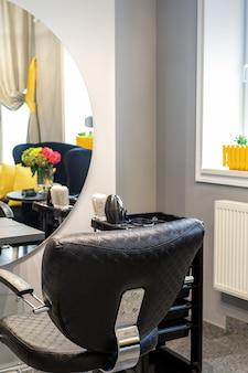 Interior de um salão de beleza. cadeira de couro preta em frente ao espelho do salão de beleza. interior de um salão de beleza