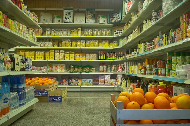 Interior de um supermercado com prateleiras cheias de mercadorias e mantimentos em exposição.