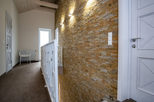 Interior de uma casa contemporânea com corredor espaçoso, portas de quarto e corrimão de escada em estilo moderno.