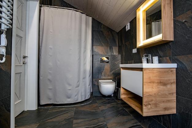 Interior de uma casa de banho moderna e elegante com paredes de azulejos pretos, cabina de duche com cortina e mobília de madeira com lavatório e grande espelho iluminado.