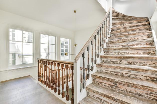 Interior de uma casa moderna com degraus de madeira e grades em uma casa moderna com grandes janelas