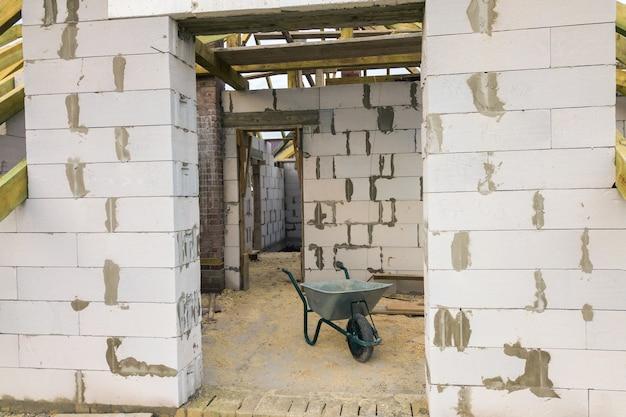 Interior de uma casa privada com paredes de tijolos de concreto aerado e moldura de madeira para telhado futuro.