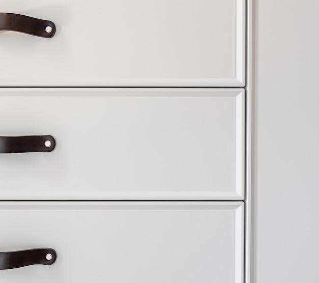 Interior de uma casa residencial moderna: detalhe dos puxadores pretos da gaveta da cozinha.