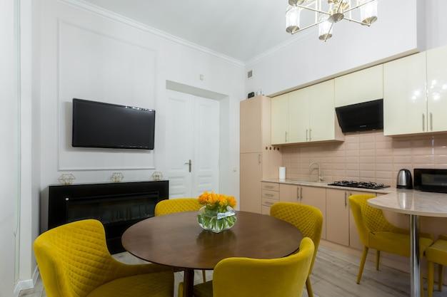 Interior de uma cozinha moderna e elegante em um pequeno apartamento, com móveis, em tons pastel, amarelo com bege