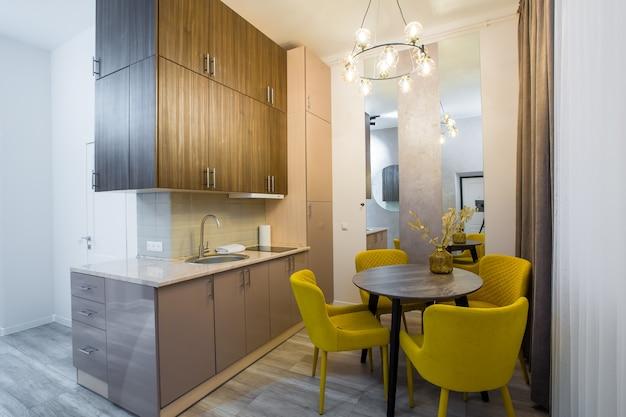 Interior de uma cozinha moderna, em um pequeno apartamento elegante, em estilo loft, com móveis