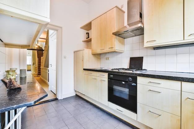 Interior de uma cozinha simples e aconchegante com armários de madeira clara e eletrodomésticos pretos à luz do dia