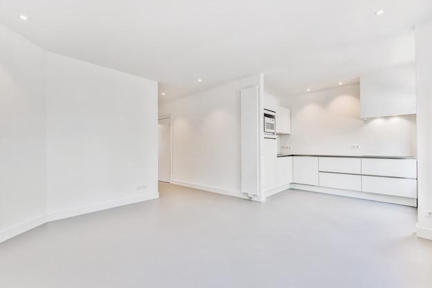 Interior de uma espaçosa sala iluminada com móveis de cozinha e área de jantar vazia em um apartamento moderno